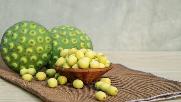 Sementes de lótus verdes em uma mesa de madeira.