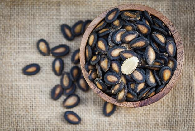 Sementes de melancia em uma tigela de madeira / sementes de melancia secas com sal para alimentos ou lanche