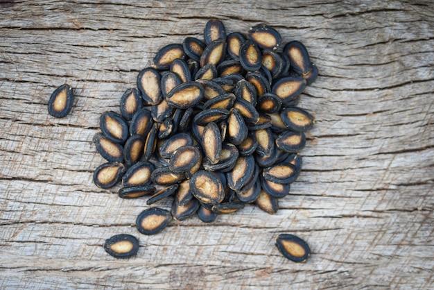 Sementes de melancia na madeira. close-up sementes de melancia secas com sal para alimentos ou lanche