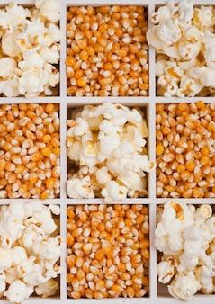 Sementes de milho doce dourado cru e pipoca em caixa de madeira branca sobre fundo claro.
