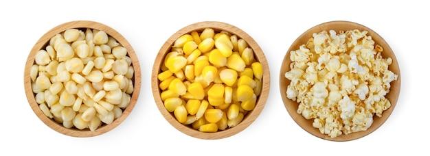 Sementes de milho, pipoca em uma tigela de madeira, isolada no fundo branco. vista do topo
