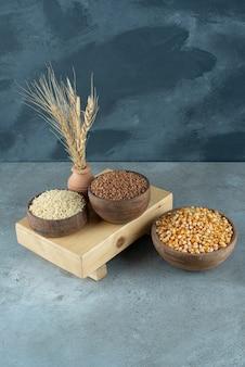 Sementes de milho, trigo sarraceno e arroz em copos de madeira. foto de alta qualidade