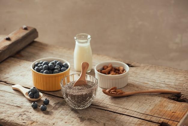 Sementes de mirtilos, amêndoas e chia frescas com leite na placa de madeira. conceito de pequeno-almoço saudável ideal.