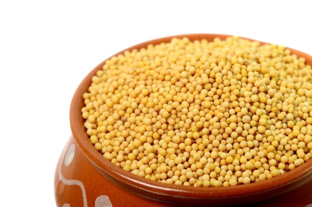Sementes de mostarda amarela em panela de barro isoladas no fundo branco