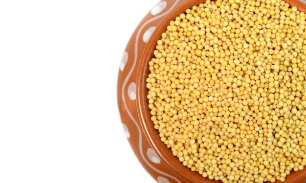 Sementes de mostarda amarela em pote de barro isolado