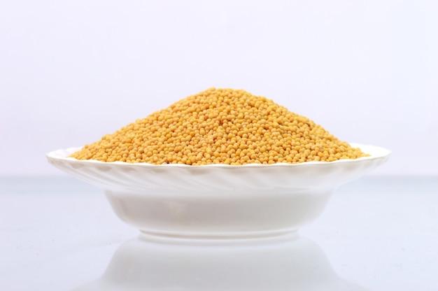 Sementes de mostarda amarela em prato isolado no fundo branco