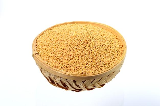 Sementes de mostarda amarela em uma cesta de madeira, isoladas no fundo branco