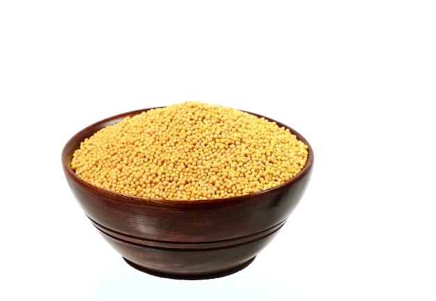 Sementes de mostarda amarela em uma tigela de madeira, isoladas no fundo branco