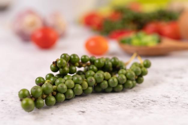 Sementes de pimenta fresca em um chão de cimento branco.