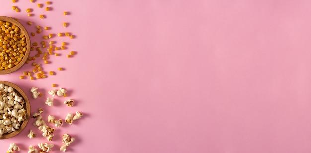 Sementes de pipoca e milho em tigelas de cortiça em fundo rosa. postura plana. copie o espaço. hora de filme.