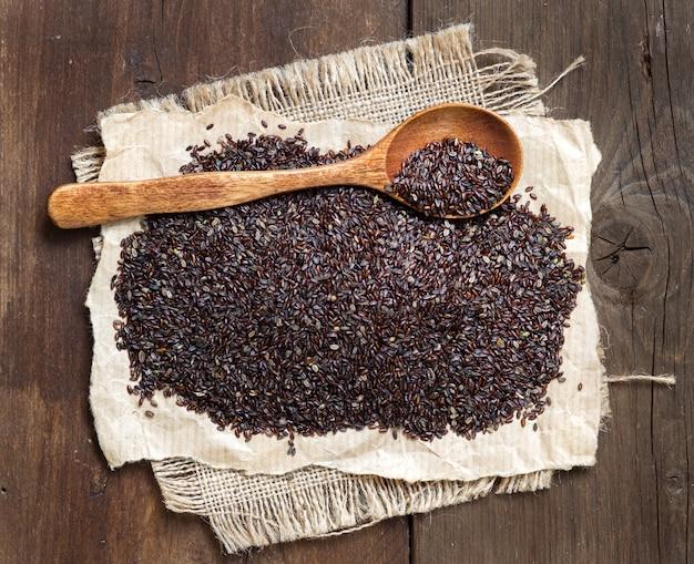 Sementes de psyllium com uma colher em uma mesa de madeira