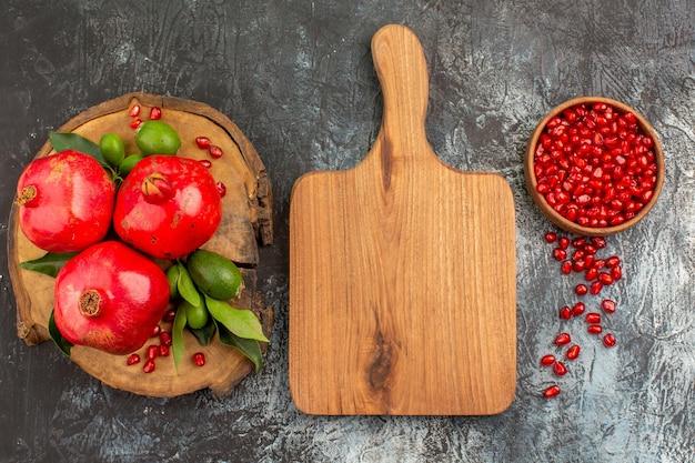 Sementes de romã de romã a tábua de cortar romãs com folhas
