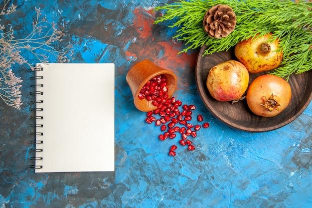 Sementes de romã de vista superior colocadas em um copo de madeira com sementes espalhadas romãs na placa de madeira galho de árvore de pinho um caderno na superfície azul