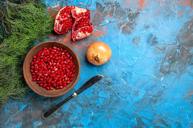Sementes de romã em uma tigela, vista de cima, faca, um galho de árvore de pinho cortado de romã na superfície azul