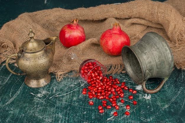 Sementes de romã espalhadas na mesa de mármore com vaso e bule.