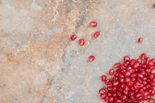Sementes de romã madura em fundo de mármore.