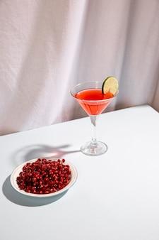 Sementes de romã madura vermelha com bebida cocktail na mesa branca