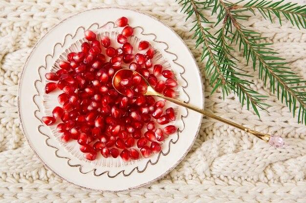 Sementes de romã no fundo de tricô de colher de ouro com vista para as copas das árvores de natal