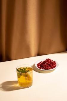 Sementes de romã vermelha brilhante com bebida cocktail na mesa branca