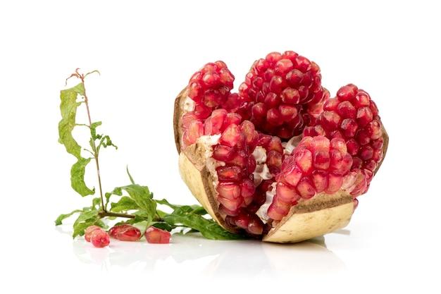 Sementes de romã vermelha em frutas isoladas no fundo branco.