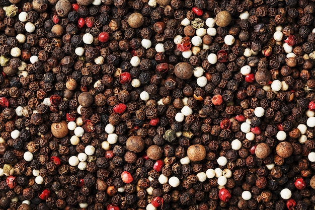 Sementes de uma mistura de pimentas com textura na parte superior em tela cheia. pimenta preta, branca, verde e rosa.
