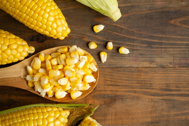 Sementes e milho doce na mesa de madeira.