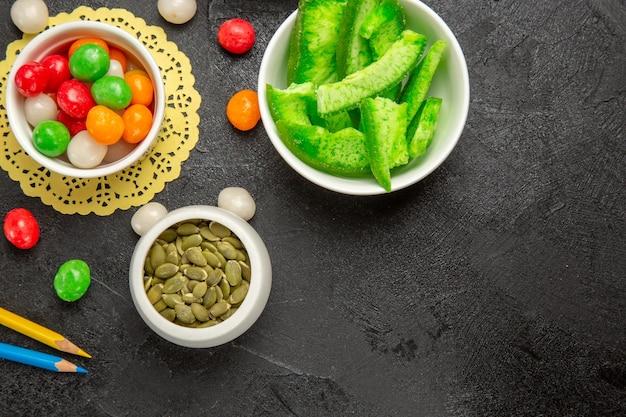 Sementes frescas de abóbora com biscoitos e balas coloridas em uma mesa cinza-escuro com sementes de arco-íris coloridas
