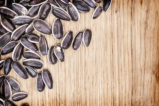 Sementes pretas com faixa branca. as sementes de girassol secas fecham-se acima na tabela de madeira com copyspace do fundo. vista do topo