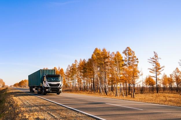 Semi-caminhão branco com contêiner na estrada de outono