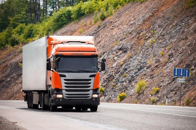Semi-caminhão laranja se movendo em uma estrada