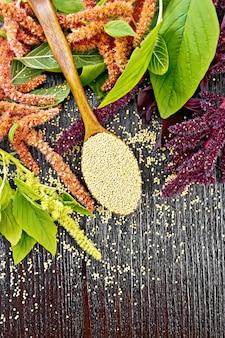 Sêmola de amaranto na colher, inflorescências vermelhas, bordô e verdes com folhas no fundo de uma tábua de madeira vista de cima