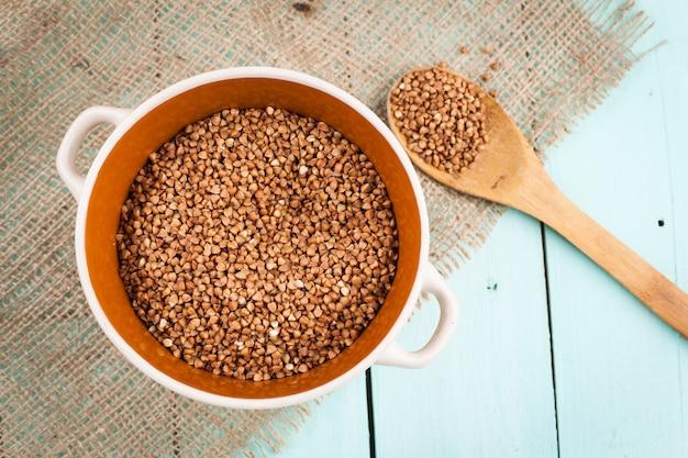 Sêmola de trigo sarraceno em uma tigela e uma colher de pau