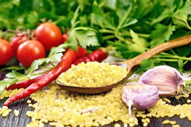 Sêmolas de bulgur - grãos de trigo cozidos no vapor - em uma colher na sacaria, tomates, pimenta, alho e salsa no fundo de uma placa de madeira escura