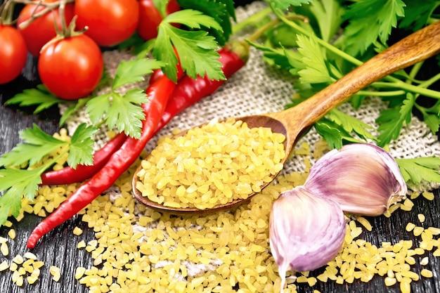Sêmolas de bulgur - grãos de trigo cozidos no vapor - em uma colher na sacaria, tomates, pimentas, alho e salsa em um fundo preto de placa de madeira