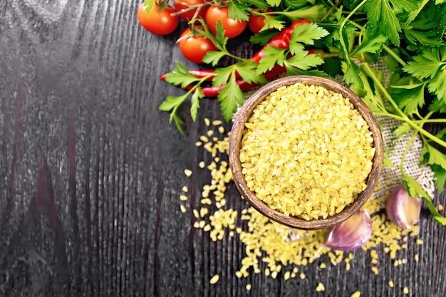 Sêmolas de bulgur - grãos de trigo cozidos no vapor - em uma tigela de barro e coloque em um guardanapo de estopa, tomate, pimenta, alho e salsa no fundo da placa de madeira de cima