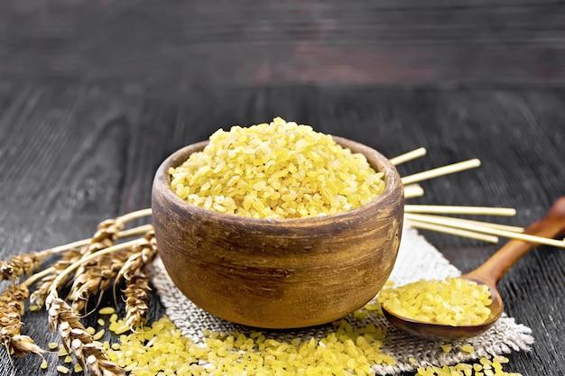 Sêmolas de bulgur - grãos de trigo cozidos no vapor - em uma tigela de barro e uma colher em um guardanapo de estopa, espigas de trigo no fundo da placa de madeira
