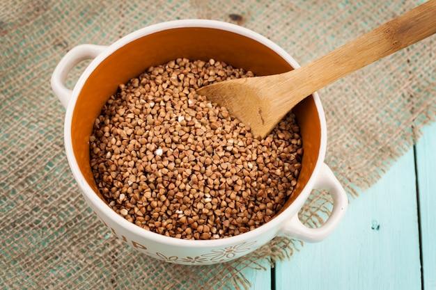 Sêmolas de trigo mourisco em uma tigela e colher de madeira