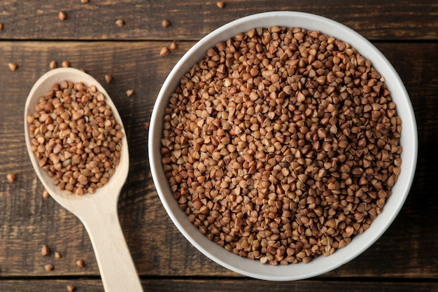 Sêmolas de trigo sarraceno secas em uma tigela branca com uma colher sobre uma mesa de madeira marrom. cereais. comida saudável. mingau. vista do topo