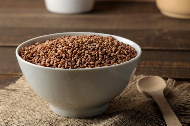 Sêmolas de trigo sarraceno secas em uma tigela branca com uma colher sobre uma mesa de madeira marrom. cereais. comida saudável. mingau.