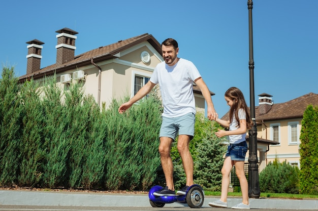 Sempre apoiando. menina encantadora segurando a mão do pai e dando apoio a ele enquanto o homem dirige uma scooter com equilíbrio