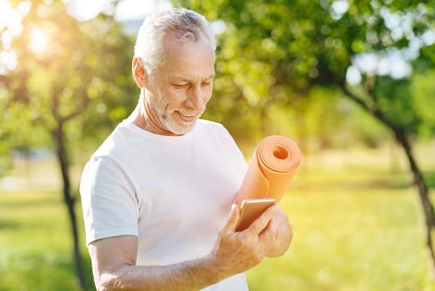 Sempre conectado. homem idoso sorridente, positivo, segurando o tapete rolante e usando um telefone inteligente
