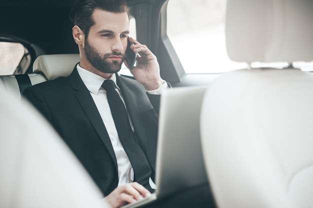 Sempre disponível. bonito e jovem empresário trabalhando em seu laptop e falando ao telefone enquanto está sentado no carro
