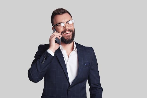 Sempre disponível. jovem bonito em trajes formais falando em seu telefone inteligente e sorrindo em pé contra um fundo cinza