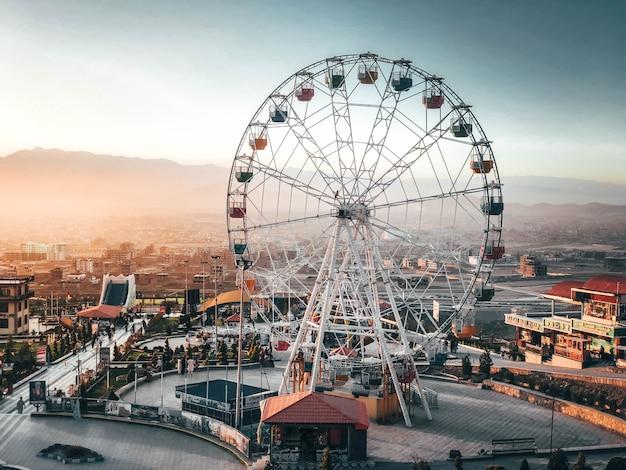 Sempre divertido ver uma roda gigante alta quando se aproxima do parque em férias cheias de pessoas felizes