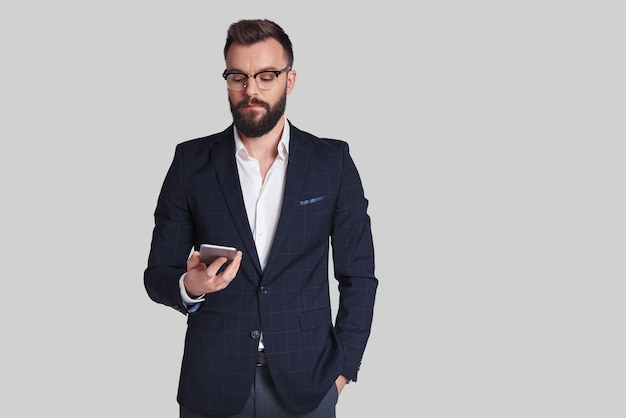Sempre em contato com os clientes. jovem bonito com terno completo usando seu telefone inteligente em pé contra um fundo cinza