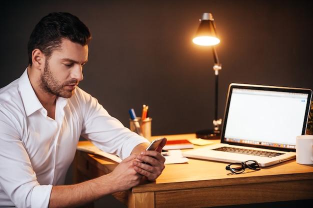 Sempre em contato. jovem confiante enviando mensagens de texto em seu telefone inteligente