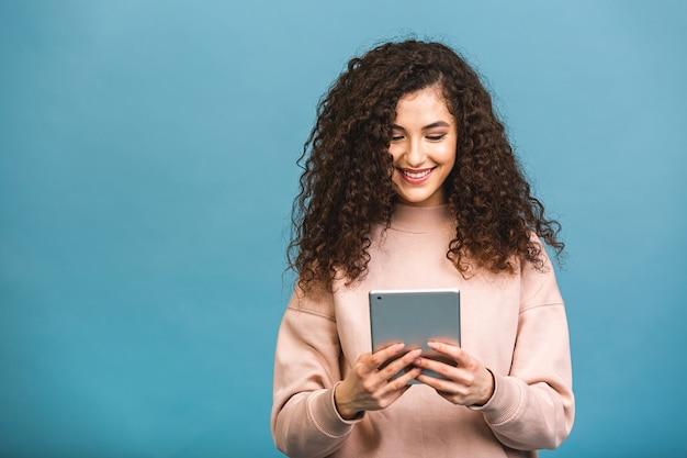 Sempre em contato! linda garota encaracolada sorrindo usando tablet isolado sobre fundo azul.