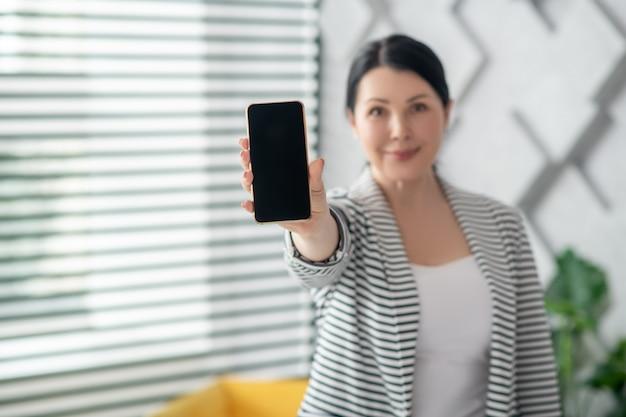 Sempre em contato. morena sorridente mulher de pé com a mão estendida, mostrando a tela do smartphone, positiva.