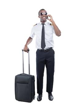 Sempre em movimento. piloto africano confiante de uniforme, apoiando a mão na mala