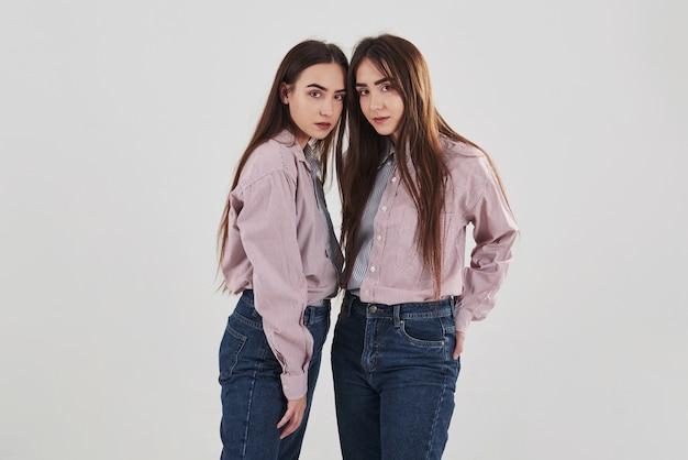 Sempre juntos. duas irmãs gêmeas em pé e posando